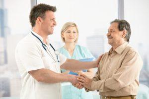 Доктор нажимает руку мужчине