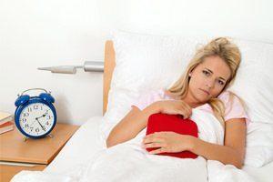 женщина лежит с грелкой на кровати