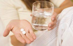 стакан с водой, в руке таблетки