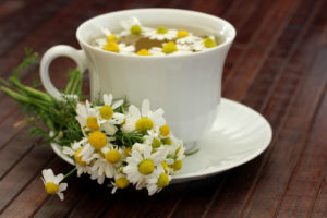 чашка с чаем из ромашек, блюдце