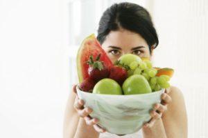 девушка держит миску с фруктами