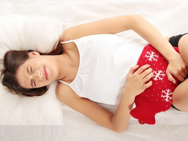 женщина лежит с грелкой