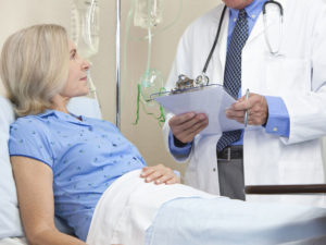 женщина на кровати, рядом доктор