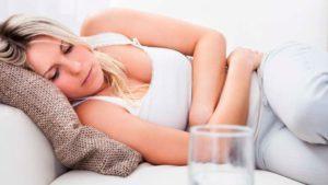 женщина лежит болеет., возле неё - стака