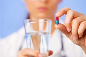 Врач держит стакан воды и таблетку