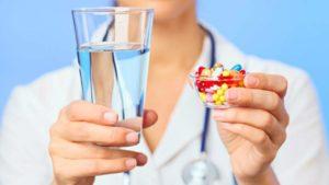 Врач держит стакан воды и таблетки