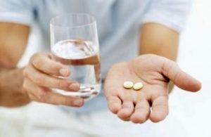 Человек пьет таблетки