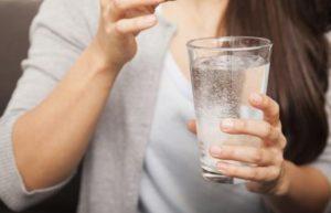 у женщины в руках стакан с содовым раствором