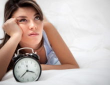 женщина лежит с будильником