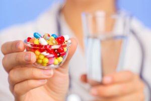Врач держит таблетки и воду в руке