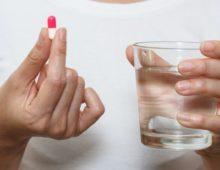 таблетка и стакан воды в руке