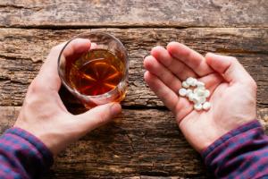 в руках алкоголь и лекарства