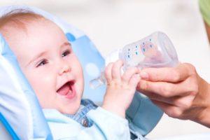 Ребенок держит бутылочку