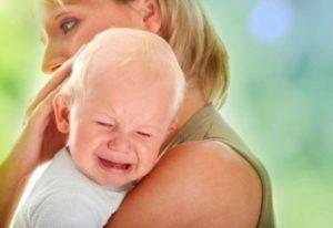 дитя плачет на руках у мамы