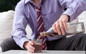 мужчина наливает в стакан алкогольный напиток