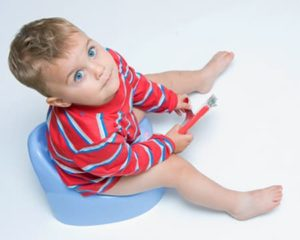 дитя сидит на горшке