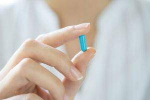 девушка держит в руках таблетку