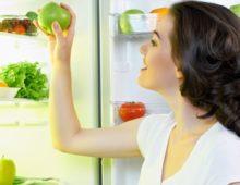 девушка достает яблоко из холодильника