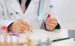 врач держит пробирку с анализом крови