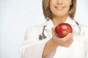 доктор держит яблоко
