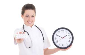 врач держит часы и таблетки