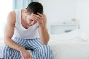 мужчина сидит на кровате
